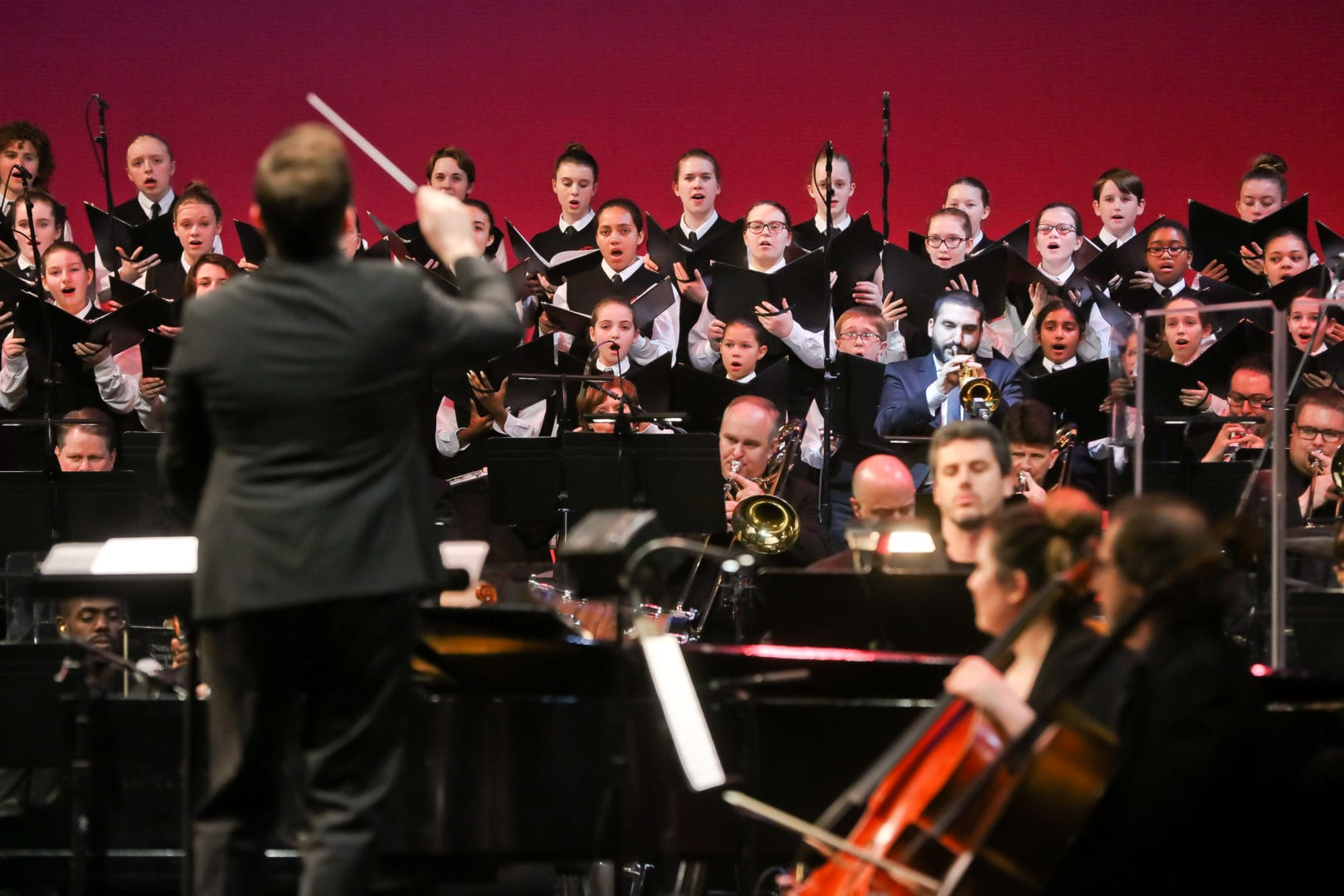 <h3>Michael Rossi conducts the orchestra, along with Ibrahim Maalouf (center-right) and the National Children's Choir.</h3>